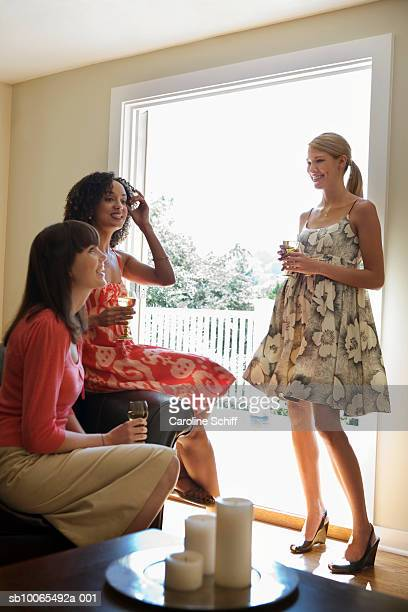 three young women drinking wine, smiling - schiff stock photos and pictures