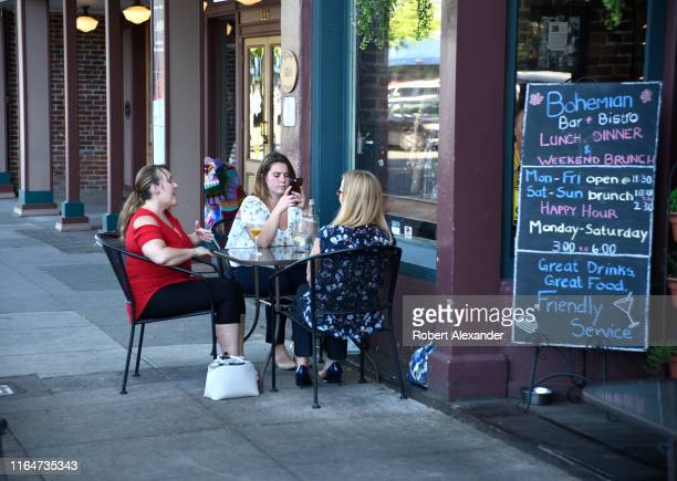 Three young women enjoy drinks and conversation around an outdoor restaurant table in Grants Pass Oregon
