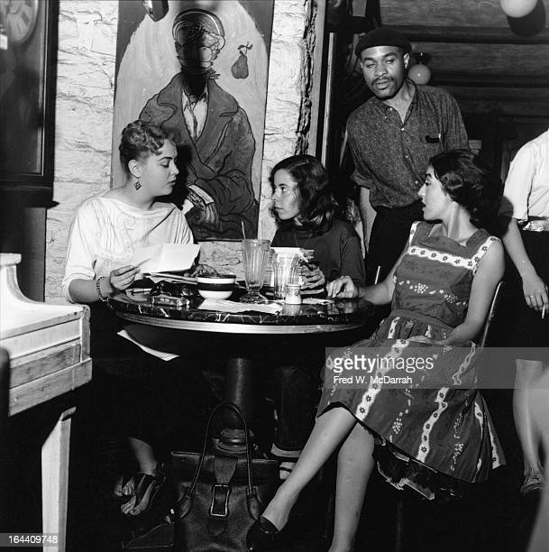 Three young women from left LSM Kelly Joan Black and Barbara Moraff sit at a table together at the Gaslight Cafe as painter poet and musician Ted...
