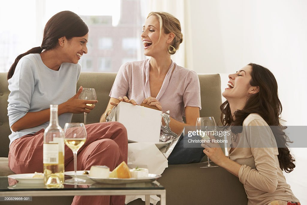 Three young women gathered on sofa, drinking wine and laughing : Stock Photo
