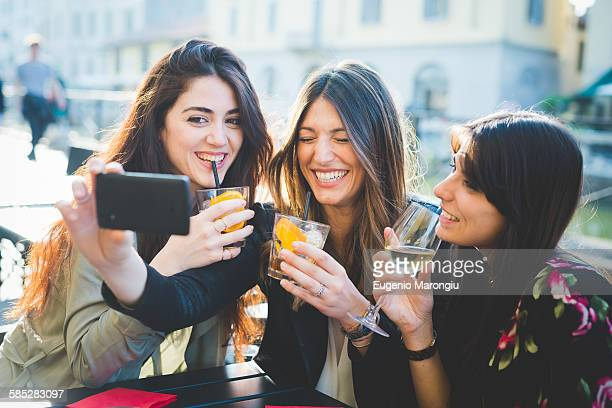 Three young women giggling for smartphone selfie at waterfront cafe