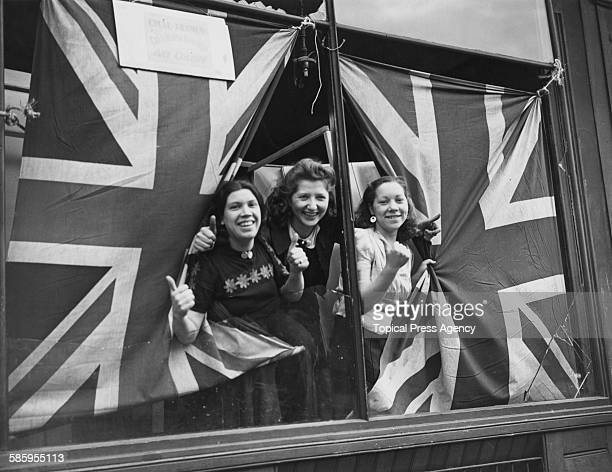 Three young women giving the thumbs-up through union jack flags, which are being used to cover the broken windows of a cycle painting shop in south...