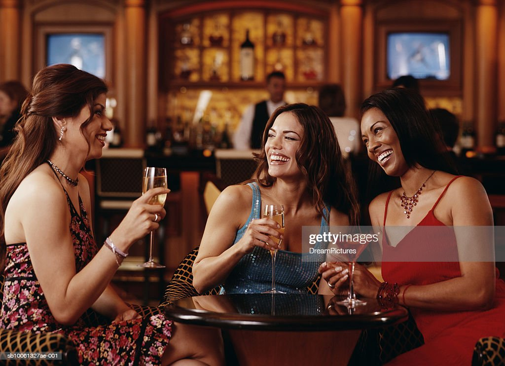Three young women having drinks in bar, smiling : Foto de stock