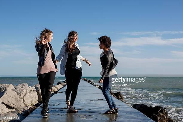 Three young women having fun on breakwater at the sea