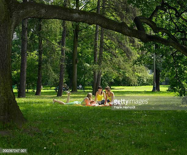 Three young women having picnic in park