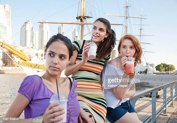 three young women having smoothies - kaltes getränk stock-fotos und bilder