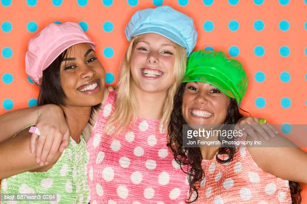 three young women holding each other smiling looking at camera - flat cap stock pictures, royalty-free photos & images