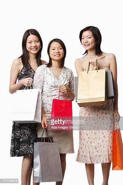 Three young women holding shopping bags