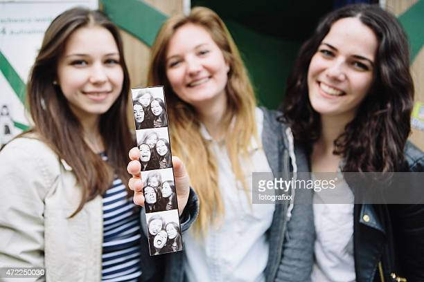 Three young women holding up pictures from a photo booth