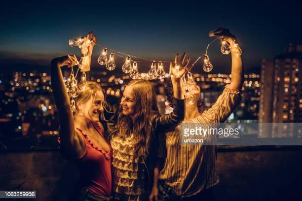 drei junge frauen umarmen auf dach - terrassenfeld stock-fotos und bilder