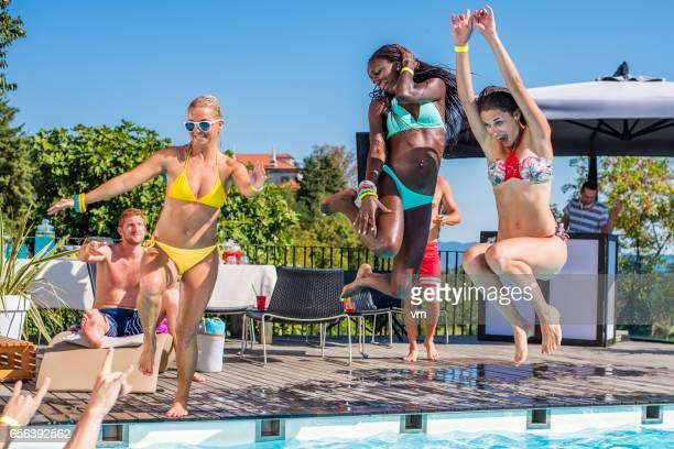Three young women in bikini jumping into pool