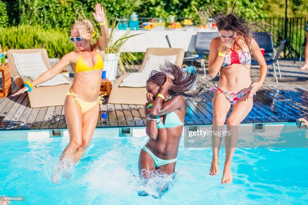 Three young women in bikini jumping into pool : Stock Photo