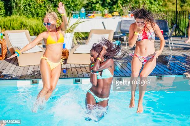 Three young women in bikini jumping into pool
