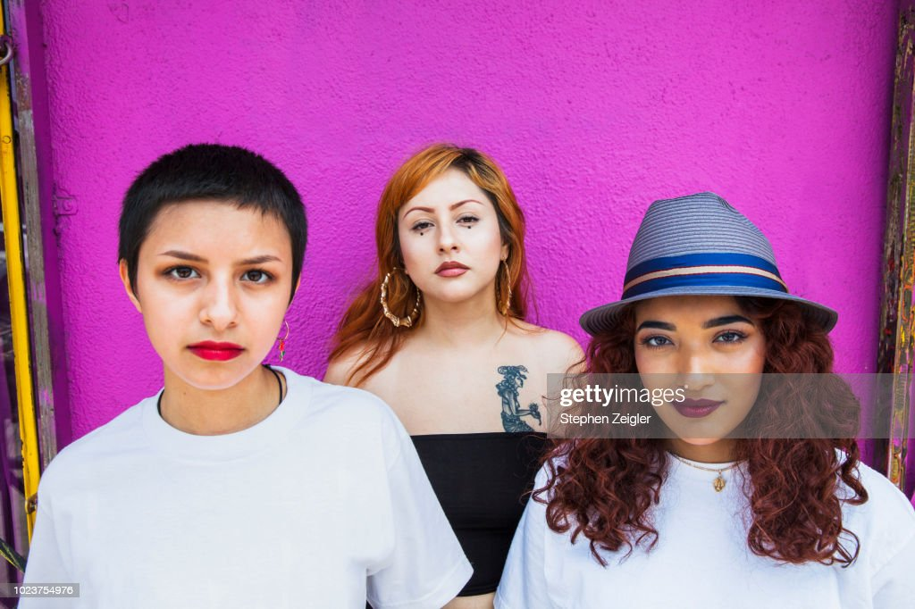 Three young women in front of pink background : Stock Photo