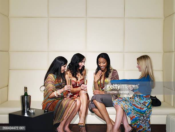 three young women in nightclub looking at woman's engagement ring - black women engagement rings stock pictures, royalty-free photos & images