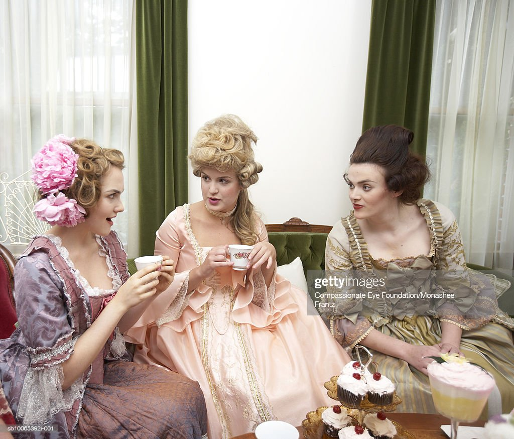Three young women in period dress talking at tea party : Foto stock