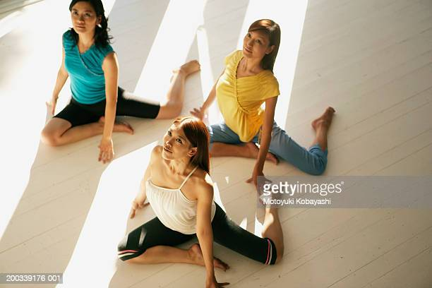 Three young women in pigeon pose, elevated view
