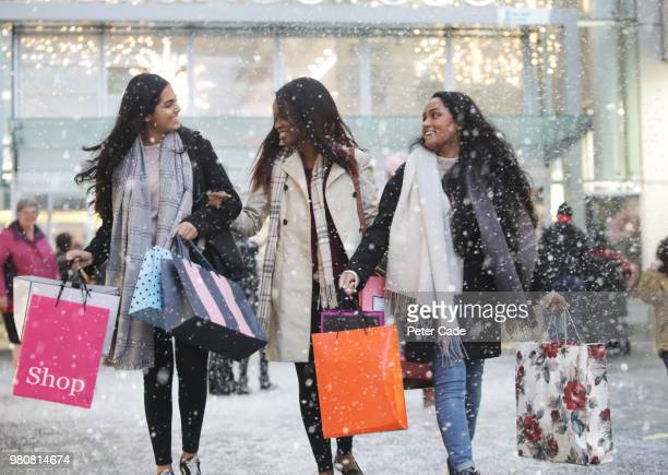 Three young women in town shopping, in the snow