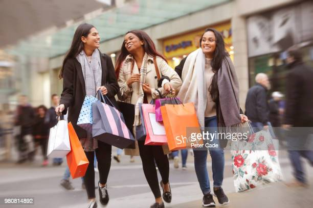 three young women in town shopping - high street stock pictures, royalty-free photos & images