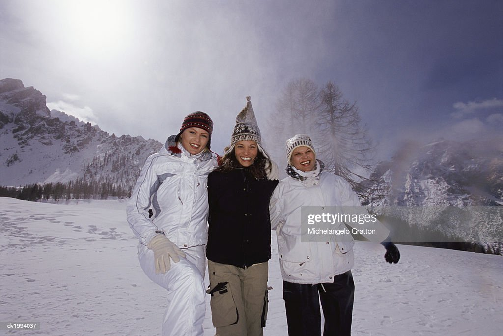 Three Young Women in Winter Clothing Standing on a Ski Slope : Stock Photo