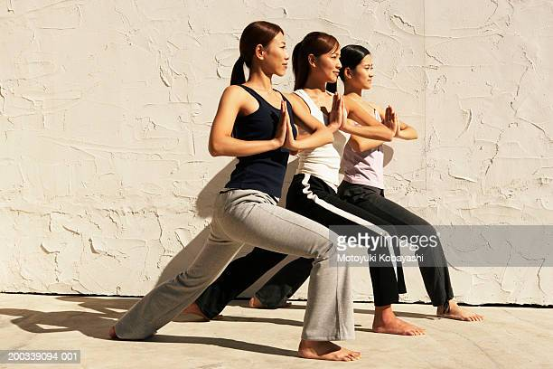 Three young women in yoga pose, side view