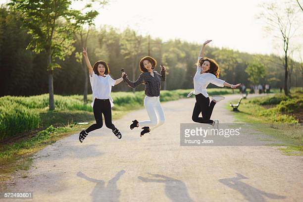 Three young women jumping for joy in park