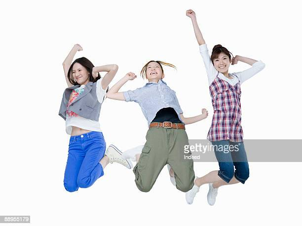 Three young women jumping in air