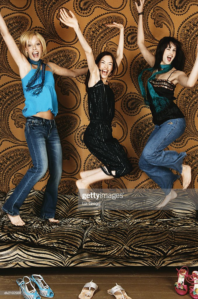 Three Young Women Jumping on a Sofa : Stock Photo