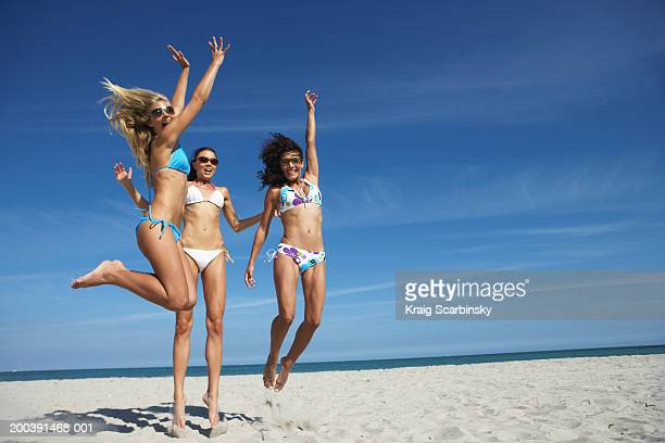 Three young women jumping on beach, portrait