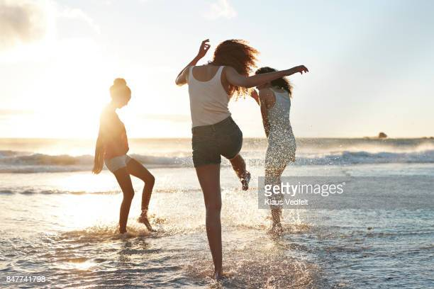 three young women kicking water and laughing on the beach - wochenendaktivität stock-fotos und bilder