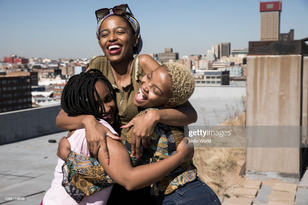 Three young women laughing and hugging on a rooftop : Stock Photo