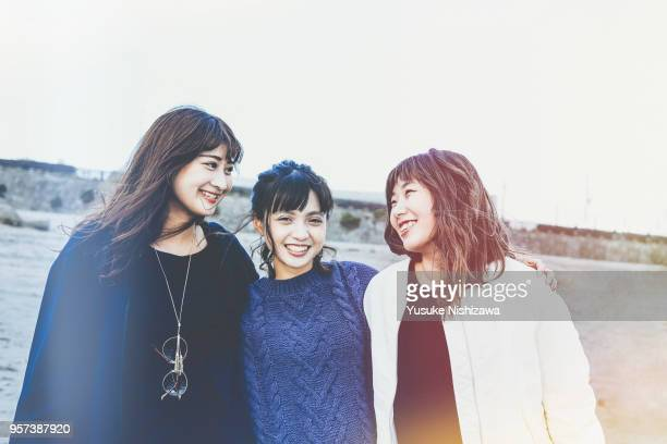 three young women laughing at the beach - three people ストックフォトと画像