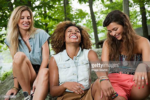 Three young women laughing in forest