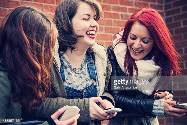three young women laughing together - leanincollection stock pictures, royalty-free photos & images