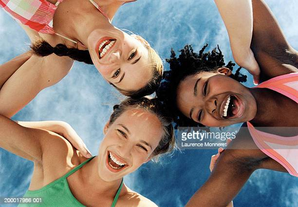 Three young women linking arms, smiling, view from below