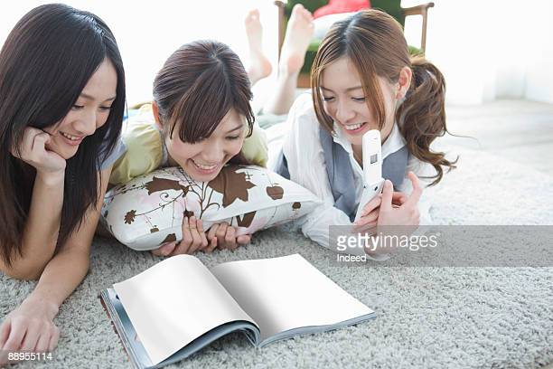Three young women looking at magazine on floor