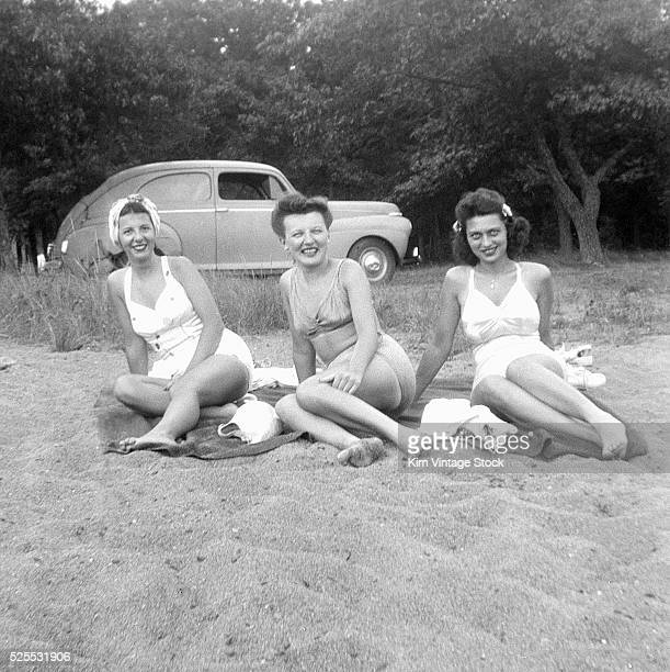 Three young women lounge on beach towels on the sand with their car in the background