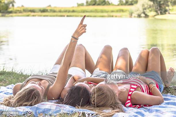 three young women lying on plaid at river or lake - 69 position stock photos and pictures