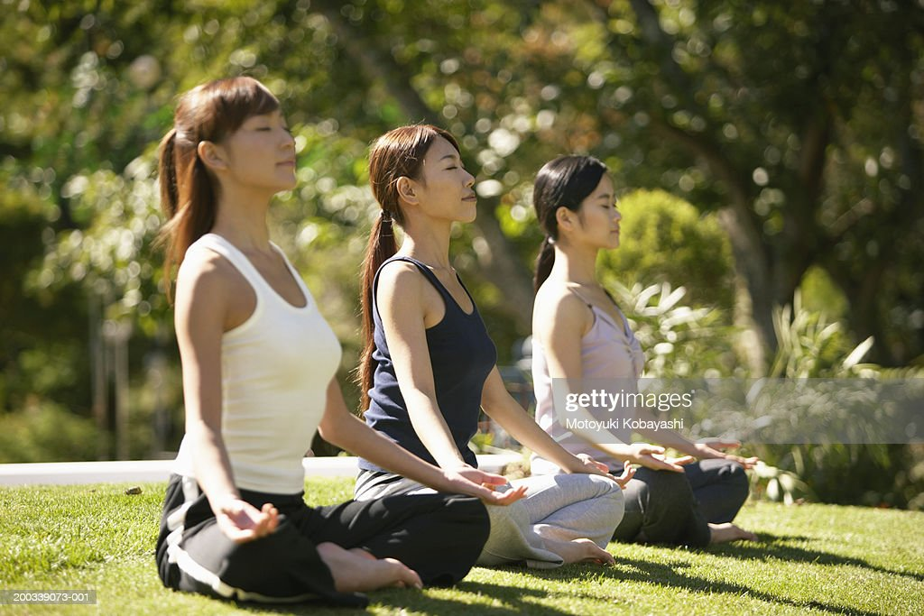 Three young women meditating, side view : Stock Photo