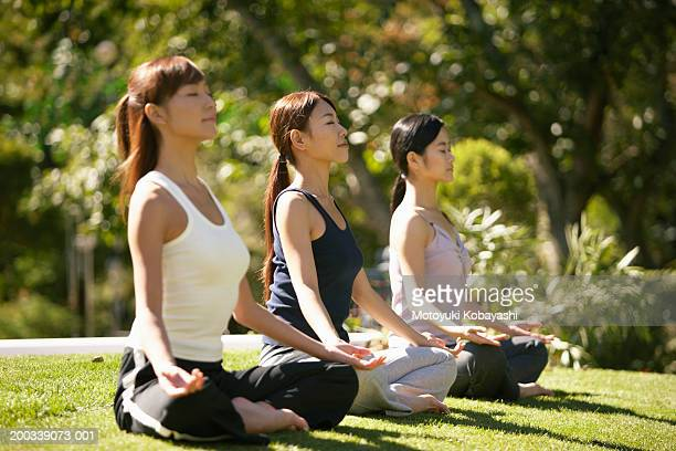 Three young women meditating, side view