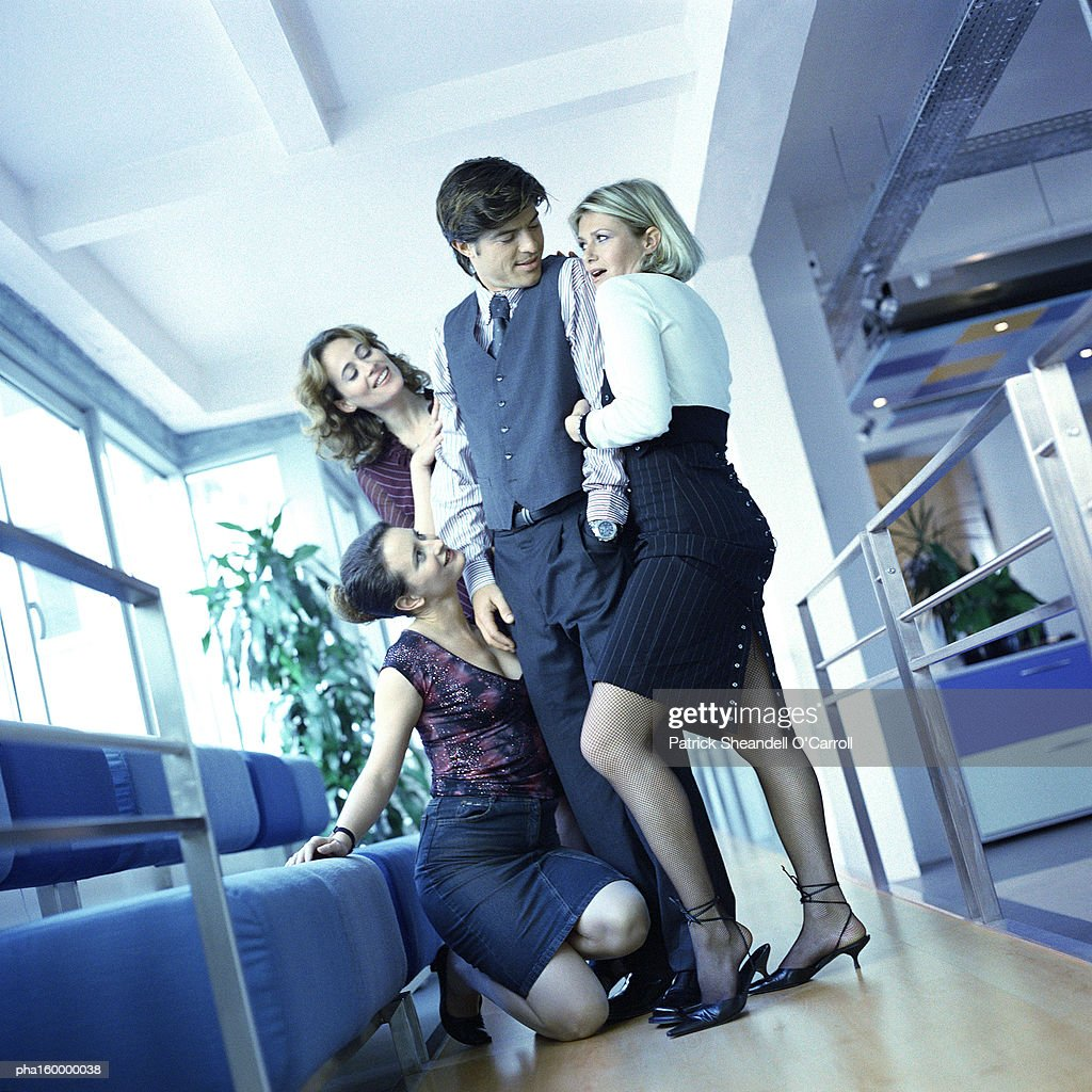 Three young women office workers surrounding male colleague. : Stock Photo