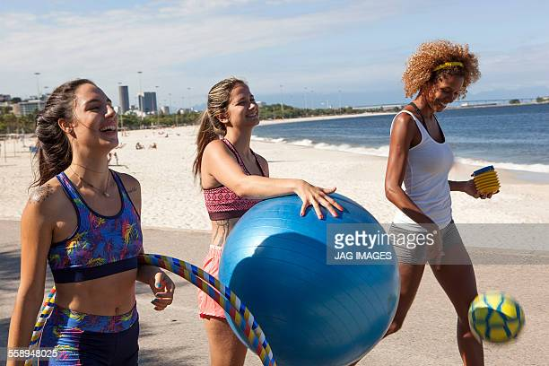Three young women on beach with fitness ball