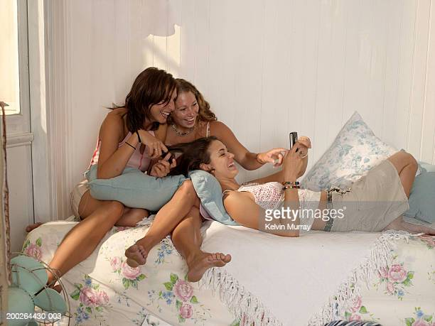 Three young women on bed, looking at mobile phone, laughing