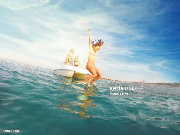 three young women on pedal boat - diving into water - pedal boat stock pictures, royalty-free photos & images