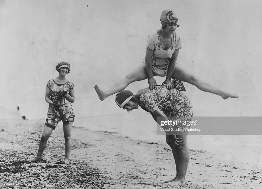 Three young women play leap frog on the beach while showing off their new jazz bathing suits, created in France, Seaview, England, early to mid 20th century.