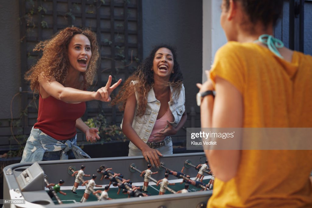Three young women playing foosball at youth hostel : Stock Photo