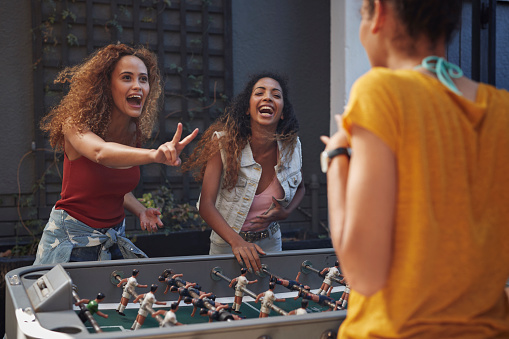 Three young women playing foosball at youth hostel - gettyimageskorea