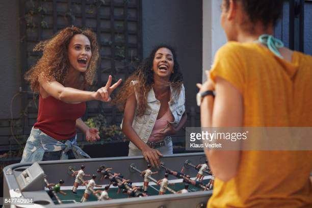 three young women playing foosball at youth hostel - wochenendaktivität stock-fotos und bilder