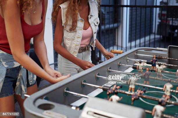 Three young women playing foosball at youth hostel