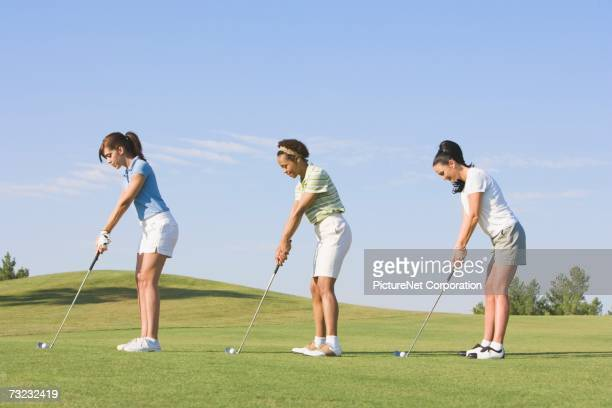 three young women playing golf on golf course - teeing off stock pictures, royalty-free photos & images